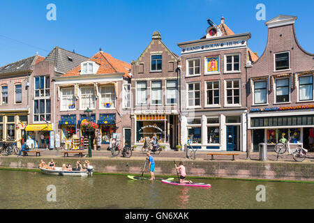 People in boat and paddle surfing on Voordam canal in Alkmaar, Netherlands - Stock Photo