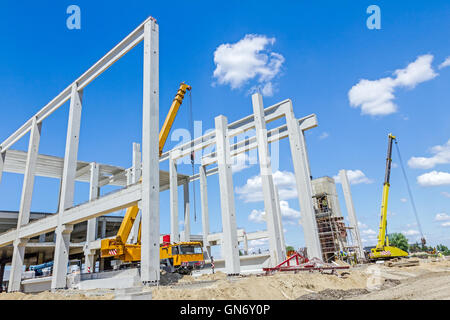 Mobile crane is working to assembly huge hall. Placing the truss on building skeleton. - Stock Photo