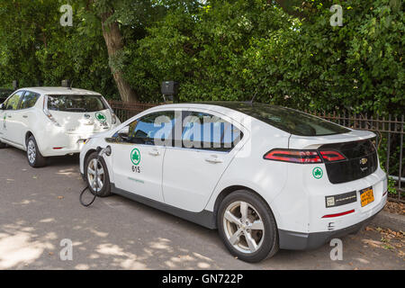 New York City Parks department Chevy Volt and Nissan Leaf electric cars receive a charge at a charging station in - Stock Photo