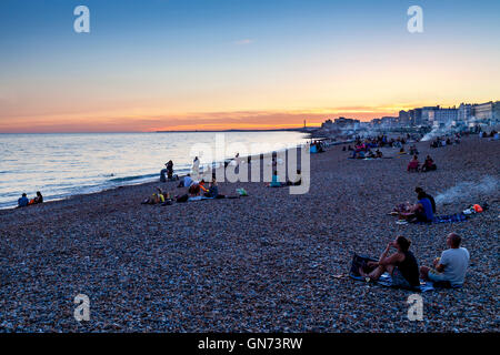 People Sitting On Brighton Beach At Sunset, Brighton, Sussex, UK - Stock Photo