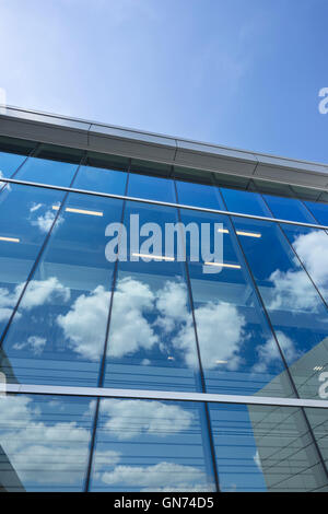 PUFFY WHITE CLOUDS BLUE SKY REFLECTED ON GLASS OFFICE BUILDING WINDOWS - Stock Photo