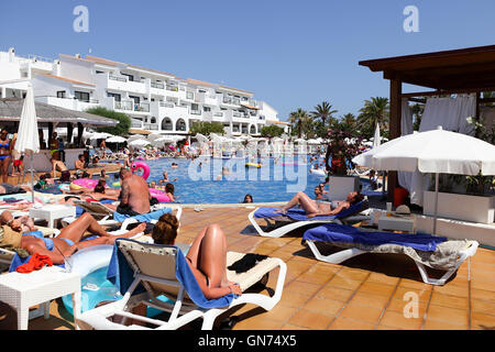 Families and holidaymakers enjoying the weather and the pool during summer holidays in Ibiza, Spain. - Stock Photo