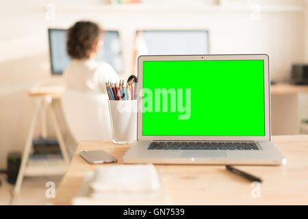 Green screen laptop computer and a glass with color pencils on wooden table, creative office on the background - Stock Photo