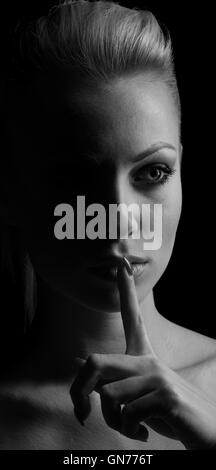 Mystery woman in shadow with finger on lips gesturing silence. Dark portrait. - Stock Photo
