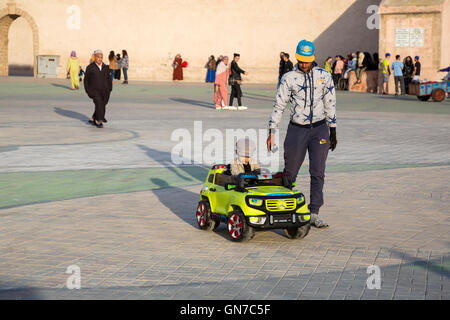 Essaouira, Morocco.  Boy Riding in Toy Car in the Place Moulay Hassan. - Stock Photo