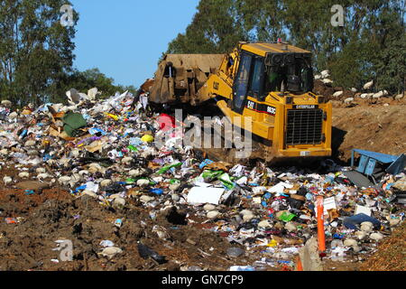 A Caterpillar 963C bulldozer pushes trash rubbish at a tip - or waste management facility - in NSW, Australia. - Stock Photo