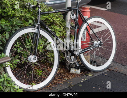 Bike chained to post - Stock Photo