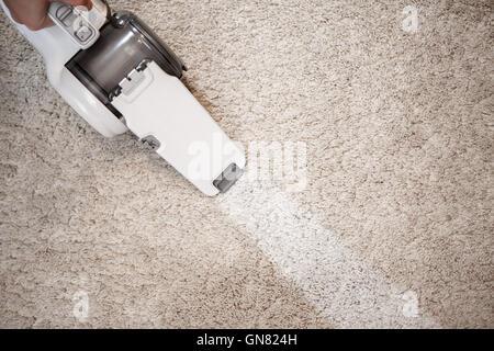 Top View Of Cordless Handheld Vacuum Cleaner On Beige Carpet