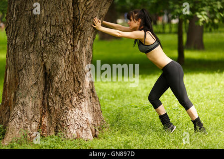 Young sporty full length girl doing stretching leaning on tree - Stock Photo