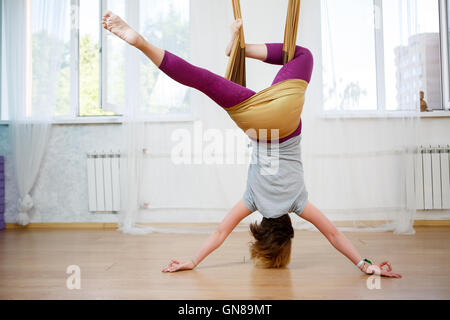 Young caucasian girl posing aerial yoga with hammock in class - Stock Photo