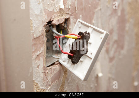 bare wiring on back of light switch in house being redecorated in the uk - Stock Photo