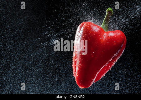 Red pepper in a spray against a black background. A series of fruits and vegetables in motion. - Stock Photo