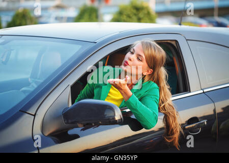 Young girl was driving the car. Business Woman in a jacket sends an air kiss. A successful and positive. - Stock Photo