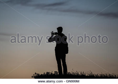 young man taking a photo with his smartphone on a cliff, heligoland, german bight, schleswig-holstein, germany, - Stock Photo