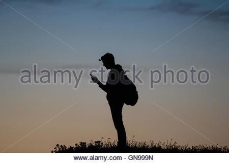 young man with his smartphone on a cliff, heligoland, german bight, schleswig-holstein, germany, north sea - Stock Photo