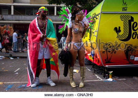 Man wearing flag with woman wearing carnival costume standing at the roadside during the 50th Notting Hill Carnival, - Stock Photo