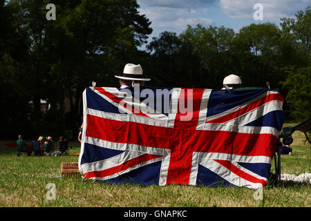 Two people sitting behind a union flag during a concert in Tenterden, Kent, England - Stock Photo
