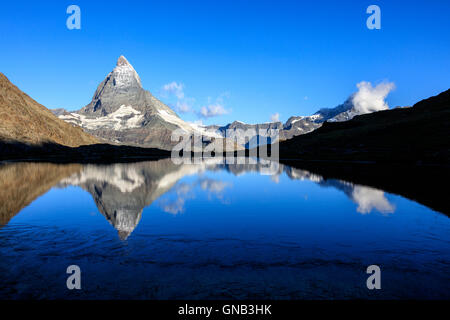 The Matterhorn reflected in the blue waters of Lake Stellisee Zermatt Pennine Alps Canton of Valais Switzerland - Stock Photo