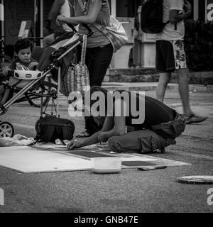 Pescara, Italy - August 13, 2016: Pescara, Italy. Woman artist drawing on the street. Black and white photography - Stock Photo