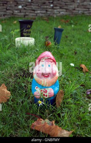 A garden gnome in a cemetery, UK - Stock Photo