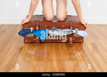 Woman trying to close overfilled suitcase - Stock Photo