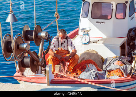 OURANOPOLIS, GREECE - JUNE 05, 2009: Native fisherman check his nets on deck of fishing boat - Stock Photo