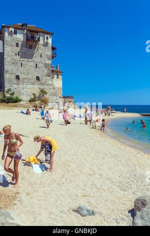 OURANOPOLIS, GREECE - JUNE 05, 2009: Tourists taking sun bath at beach near Phospfori tower - Stock Photo