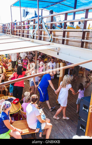OURANOPOLIS, GREECE - JUNE 05, 2009: Tourists dancing Sirtaki at deck of touristic cruise ship - Stock Photo