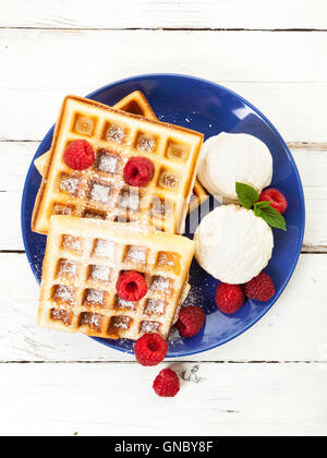Belgian waffles with raspberries, vanilla ice cream scoops and powdered sugar on blue plate, on rustic wooden table, - Stock Photo
