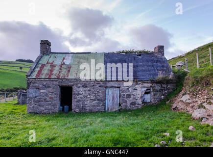 An old cottage on a farm near Cushendun, now used for storage. - Stock Photo