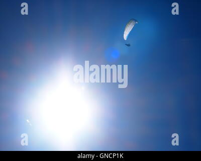 paraglider with white canopy flying high in a deep blue sky with the sun bright and reflecting off the canopy - Stock Photo