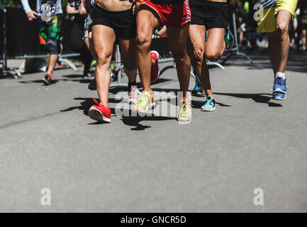 Running people on crossfit competition, feet on the road close up photo - Stock Photo
