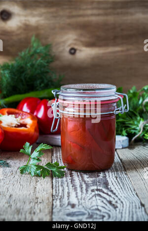 Homemade  pickled peppers in tomato juice and sweet bell red pepper on rustic table - Stock Photo
