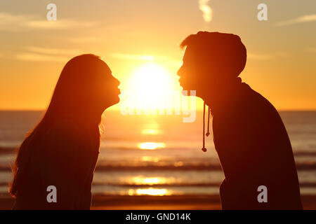 Side view of a couple silhouette of teenagers kissing the sun with love at sunset on the beach with the horizon - Stock Photo