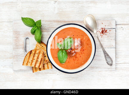 Cold gazpacho tomato soup in bowl with toasted bread - Stock Photo