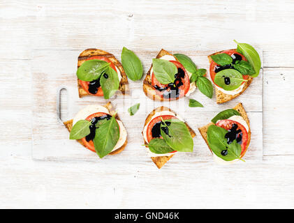 Caprese sandwiches with tomato, mozzarella cheese, basil and balsamic glaze on white painted wooden background - Stock Photo