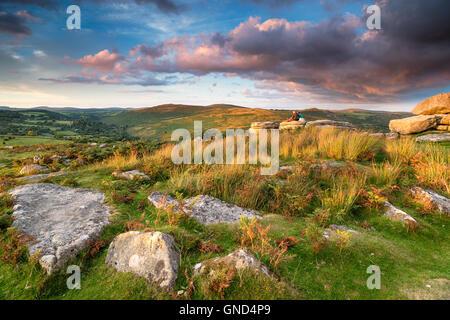 Watching the sunset from Combestone Tor near Hexworthy on Dartmoor National Park in Devon - Stock Photo