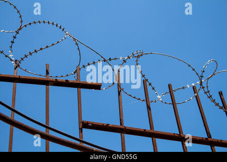 Enlightened barbed wire on the top of a metal fence. Bright blue sky in the background. - Stock Photo