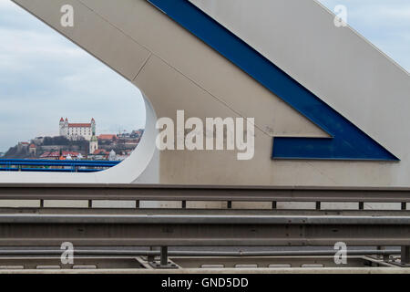 Shape of a modern bridge Apollo with a blue detail. In the background the downtown of Bratislava with the castle - Stock Photo