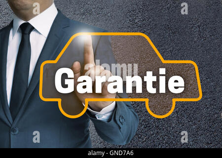 garantie (in german warranty) auto touchscreen is operated by businessman concept. - Stock Photo