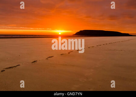 Sun setting behind Burry Holms, from Rhossili Beach. - Stock Photo