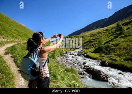 Woman taking a picture of the Ferrand river in the Alps with her mobile, Valley Ferrand, Oisans, France, Oisans, France, Europe.