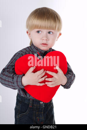 little boy holds heart isolated on white - Stock Photo
