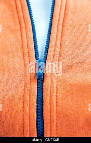 blue zipper on fashionable orange warm wear - Stock Photo