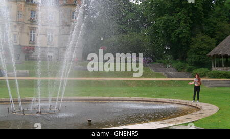 Young Girl Cooling Off In The Fountain At Bagnoles De LOrne - Stock Photo