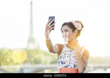 Paris, Woman doing a selfie with Eiffel Tower in Background - Stock Photo