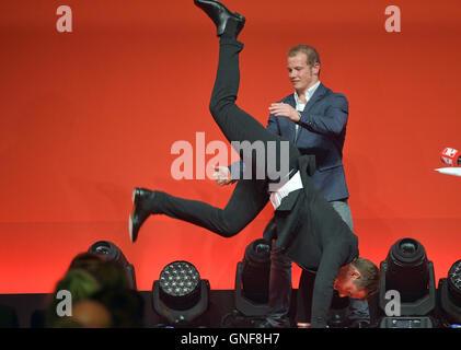 Gold medalist Fabian Hambuechen lets presenter Alexander Bommes show a handstand at the Sport Bild-Award ceremony - Stock Photo