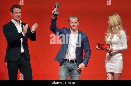 Hamburg, Germany. 29th Aug, 2016. Gold medalist Fabian Hambuechen celebrates his award with presenters Andrea Kaiser - Stock Photo