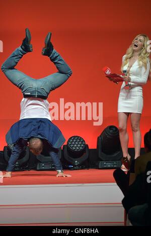 Gold medalist Fabian Hambuechen shows presenter Andrea Kaiser a handstand at the Sport Bild-Award ceremony in Hamburg, - Stock Photo