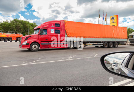 Big american truck on the highway. View from the car window - Stock Photo